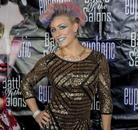 Angelique Kenney in a black-golden dress and pink hair poses at a photoshoot in an event.
