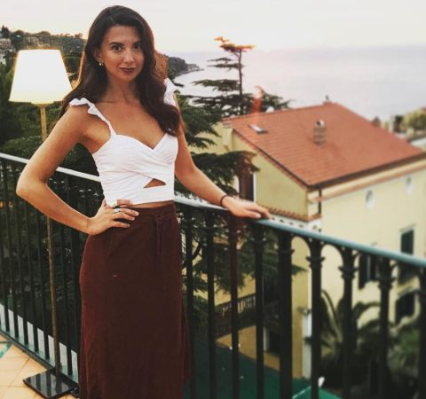 Zizi Strallen in a white dress poses for a photo.