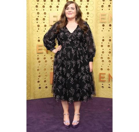 Aidy Bryant in a black dress poses at the Emmy award ceremony.