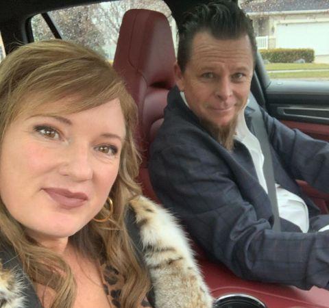 Charity Kindig in a white dress poses for a selfie alongside husband Dave Kindig.
