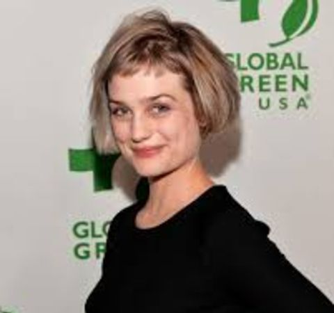 Alison Sudol in a black t-shirt poses for a picture.