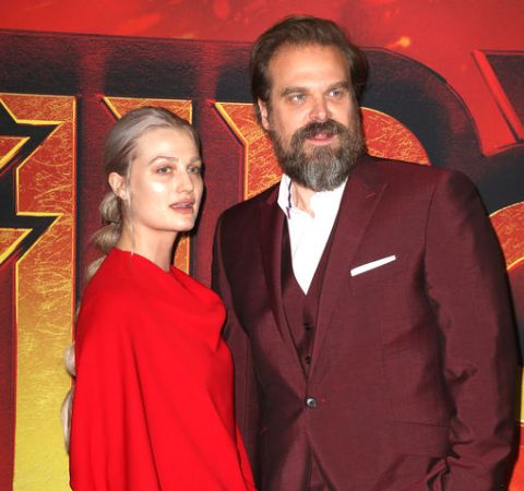 Alison Sudol in a red dress poses alongside the multi-talented David Harbour.
