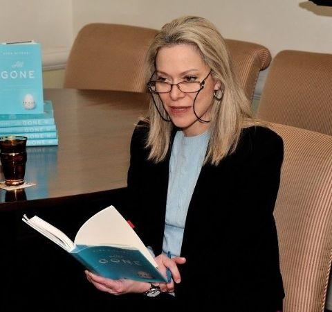 Alex Witchel in a black coat reading her novel All Gone.