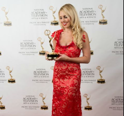 Jenn Barlow in a red dress poses with her Emmy Award.