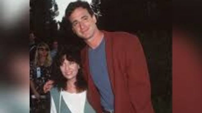 Sherri Kramer in a white dress poses alongside comedian husband Bob Saget.