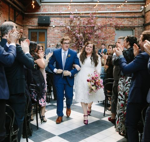 Aidy Bryant and husband Conner O'Malley walk down the aisle in their wedding ceremony.