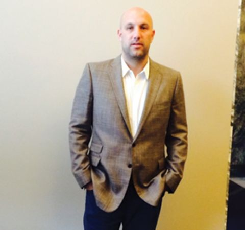 Rich Kleiman in a grey suit poses for a picture.