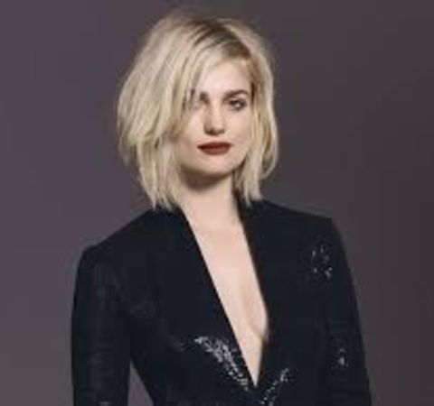 Alison Sudol in a black coat poses at a photoshoot.