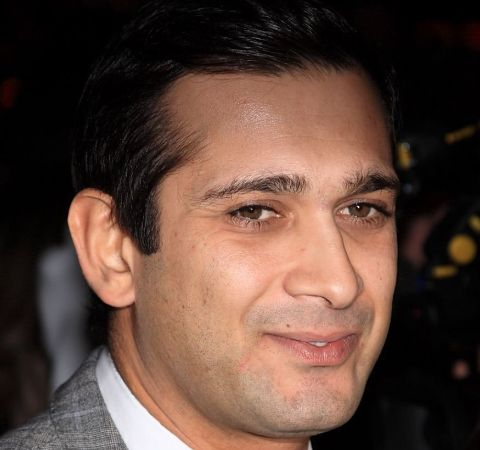 Jimi Mistry in a grey suit poses for a picture.
