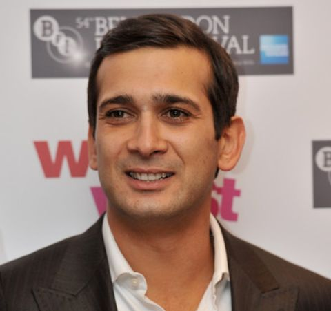 Jimi Mistry in a black suit poses for a photoshoot at an event.