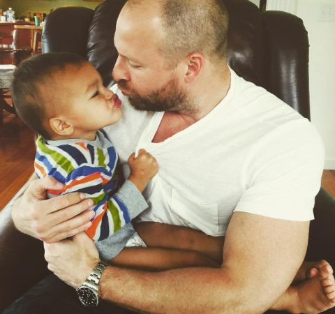 Ryen Russillo in a white t-shirt poses with a baby.