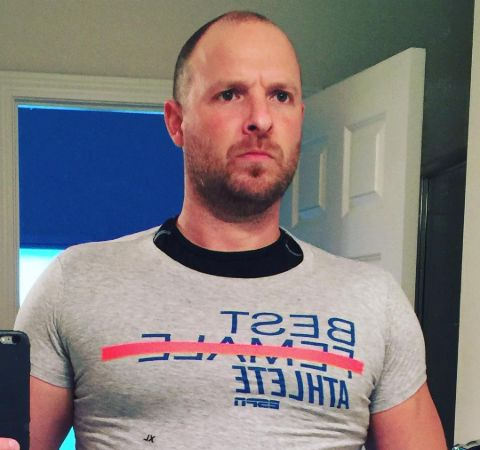 Ryen Russillo in a grey t-shirt poses for a picture.