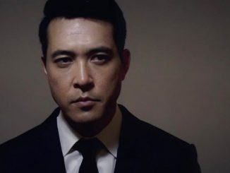 Jonathan Ohye in a black suit poses for a photoshoot.
