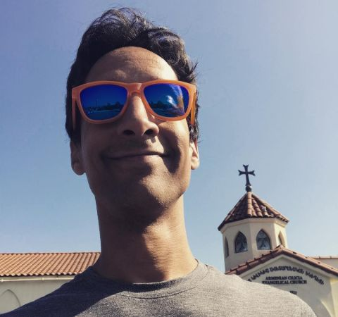 Danny Pudi in a grey t-shirt poses for a selfie.