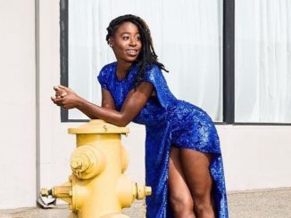 Kirby Howell Baptiste in a blue dress poses for a picture.