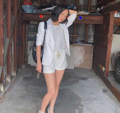 Charlotte Nicdao in a white dress poses for a picture.