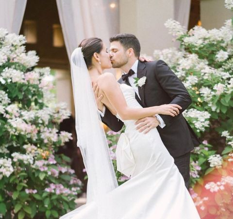 Jerry Ferrara in a black tuxedo kisses his bride Breanne Racano.