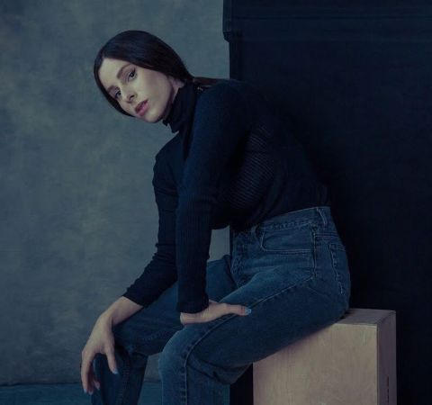 Sasha Spielberg in a black top and blue jeans poses for a picture.