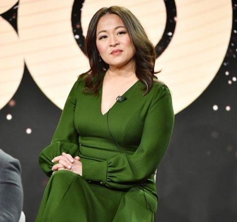 Suzy Nakamura  in a green dress poses for  a picture.