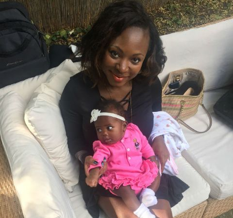 Naturi Naughton in a black dress poses with her baby  daughter in pink.