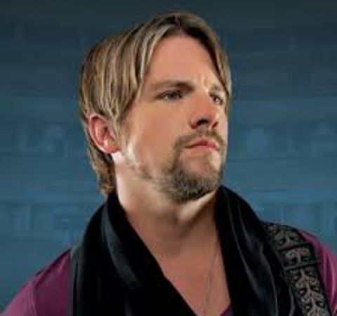 Zachary Knighton in a dark pink t-shirt poses for a picture.