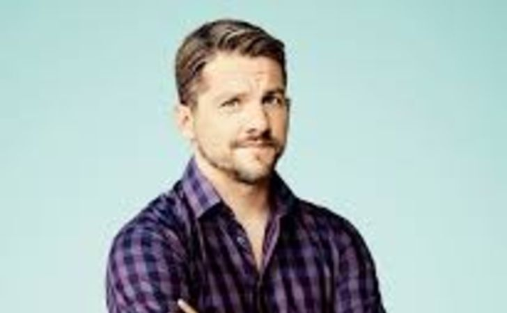 Zachary Knighton in a pink shirt poses for a picture.