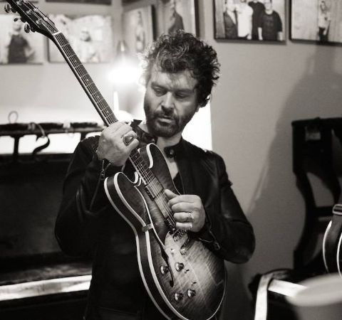 Doyle Bramhall in a black t-shirt holding his guitar.