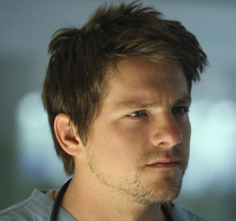 Zachary Knighton in a grey shirt poses for a picture.