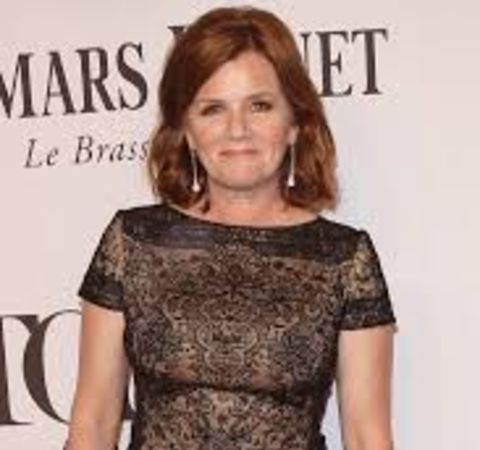 Mare Winningham in a black cloth poses for  a picture.