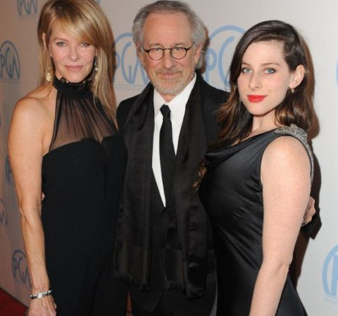 Sasha Spielberg in a black dress at right poses with her dad Steven Spielberg.