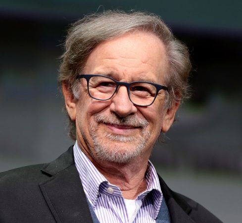 Steven Spielberg in a black suit poses for a picture