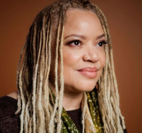 Kasi Lemmons in a black dress and blonde hair poses for a picture.