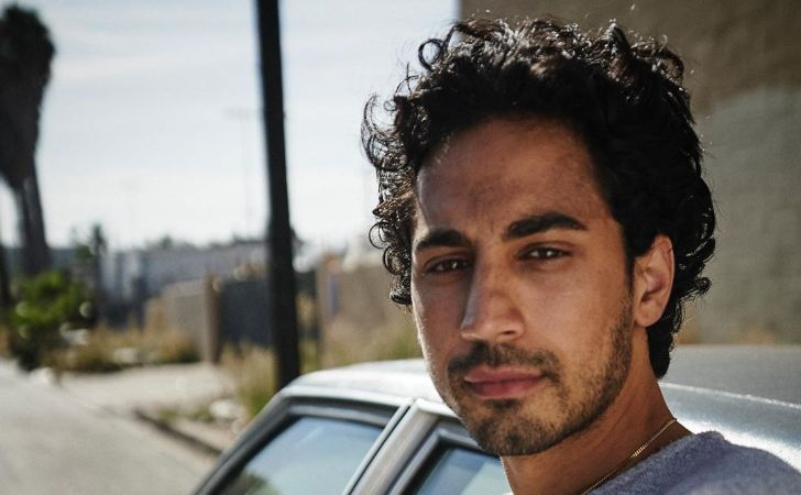 Andres Joseph poses a picture in front of a car.