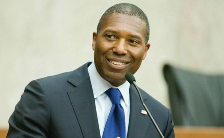 Tony West in a black suit poses for a picture.