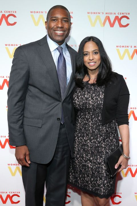 Tony West in a black suit poses a picture with Maya Harris.