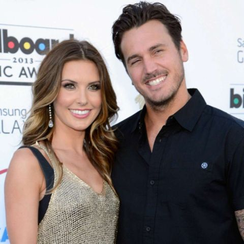 Corey Bohan in a black t-shirt poses a picture with her ex-wife Audrina Patridge.