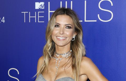 Audrina Patridge in a green top poses for a picture.