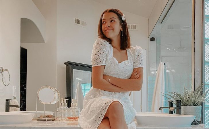 Klailea Bennett in a white dress poses a picture.