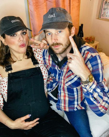 Molly Tarlov in a black dress poses for a picture with husband.