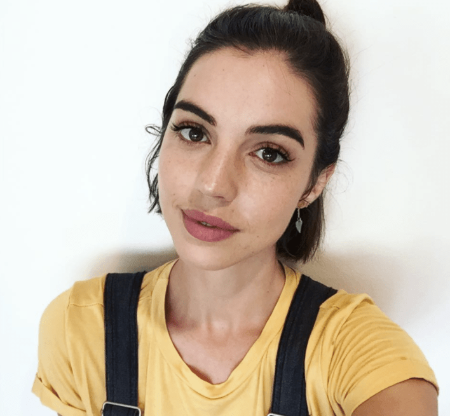 Adelaide Kane in a yellow dress poses for a picture.