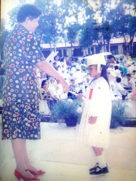 Jonha receiving a grade school diploma during their graduation