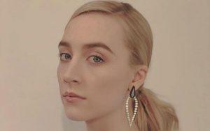 Saoirse Ronan posing for a photo wearing earings