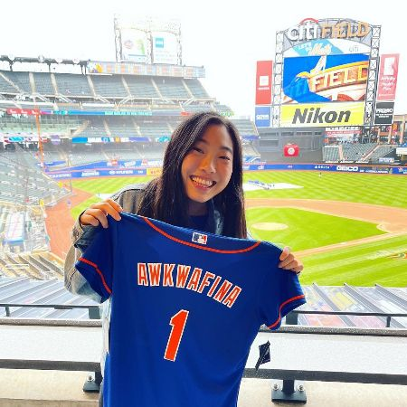 Awkwafina holding her favorite Mets jersey