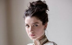 Eve Hewson wearing a white dress and posing for a photo.
