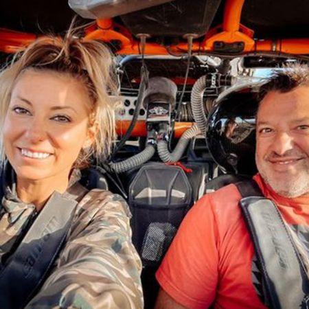 Pennelope and her husband inside his racecar