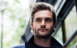 Tom Bateman wearing a black cardigan and posing for a photo.