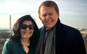 Debi Segura with her husband Lou Dobbs wearing sunglasses and smiling