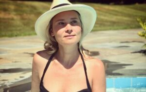 Kristina Klebe wearing a black swimsuit and hat and posing for a photo.