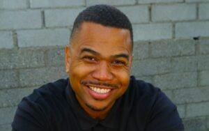 Omar Gooding wearing a black t-shirt and posing for a photo.