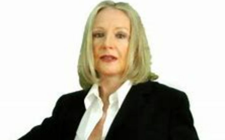 Alexandra Lorex wearing a black suit and white t-shirt and posing for a photo.